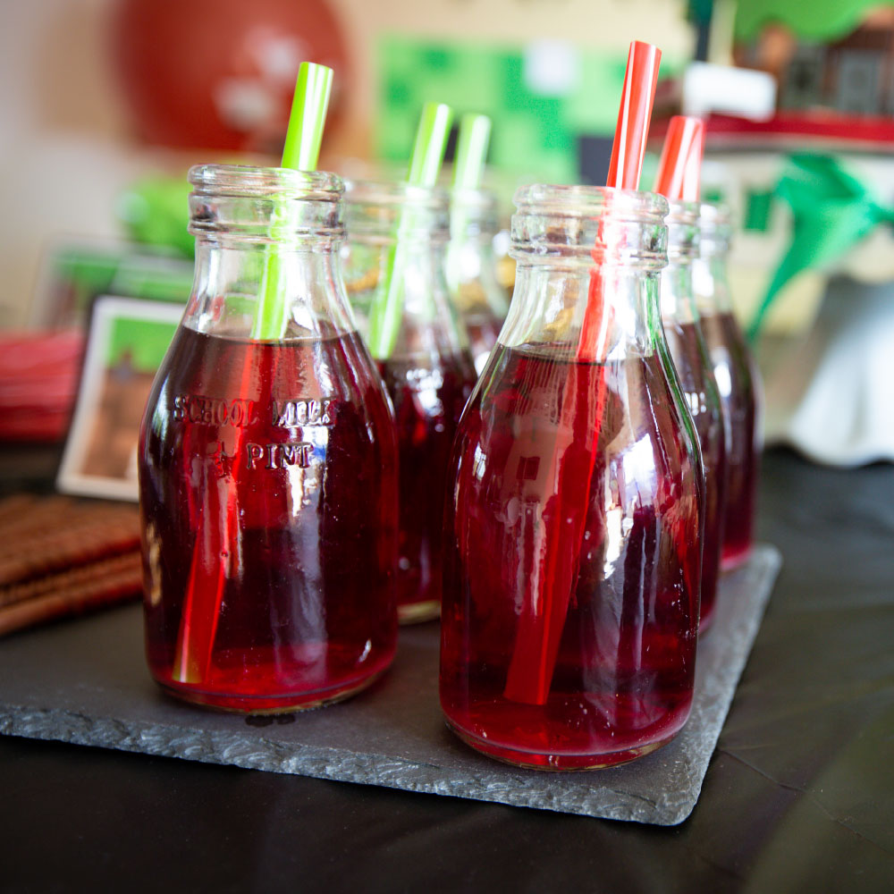 Red drinks in glass bottles and a straw