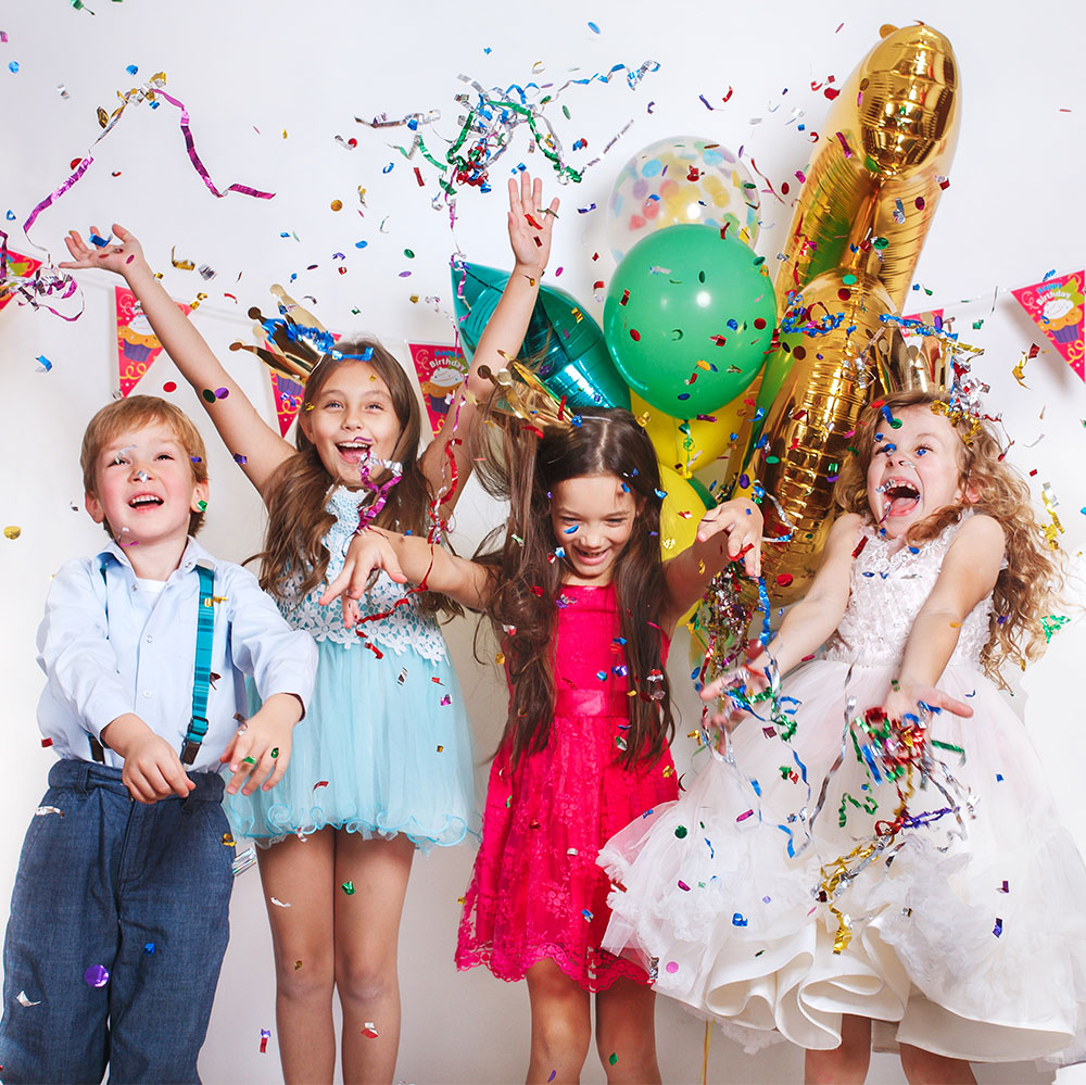 4 children enjoying a children't birthday party with balloons and confetti