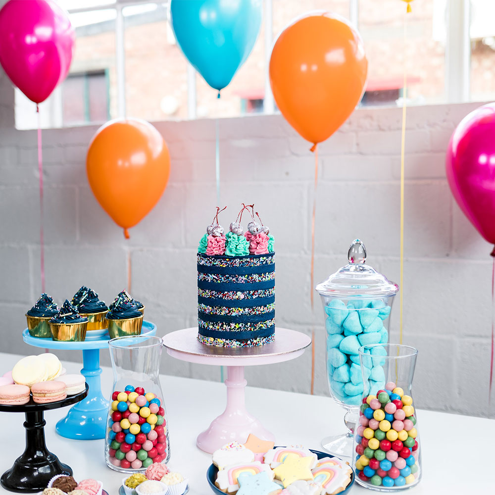 Children's birthday party table with cake sweets and balloons