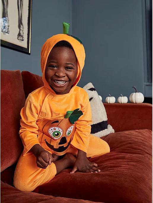 Little boy dressed in a Halloween pumpkin onesie