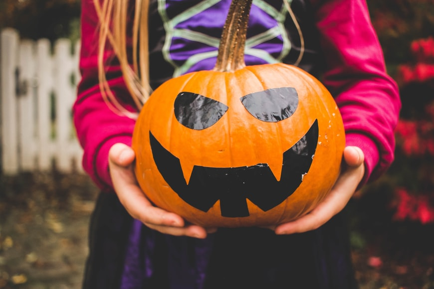 Girl holding a scary pumpkin